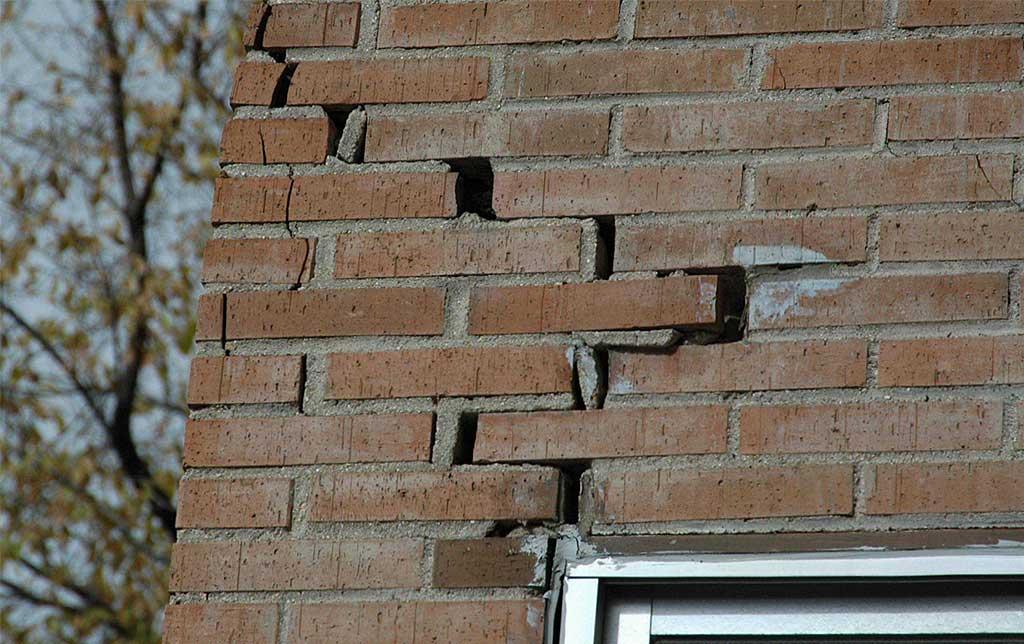 Lesiones en fachada de ladrillo. Grietas.
